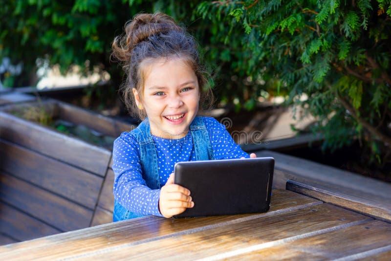 在片剂的愉快的女孩戏剧户外 工作外面与 免版税库存照片