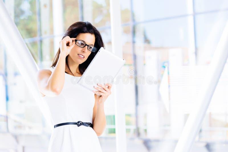 在片剂的现代女实业家读书 免版税库存照片