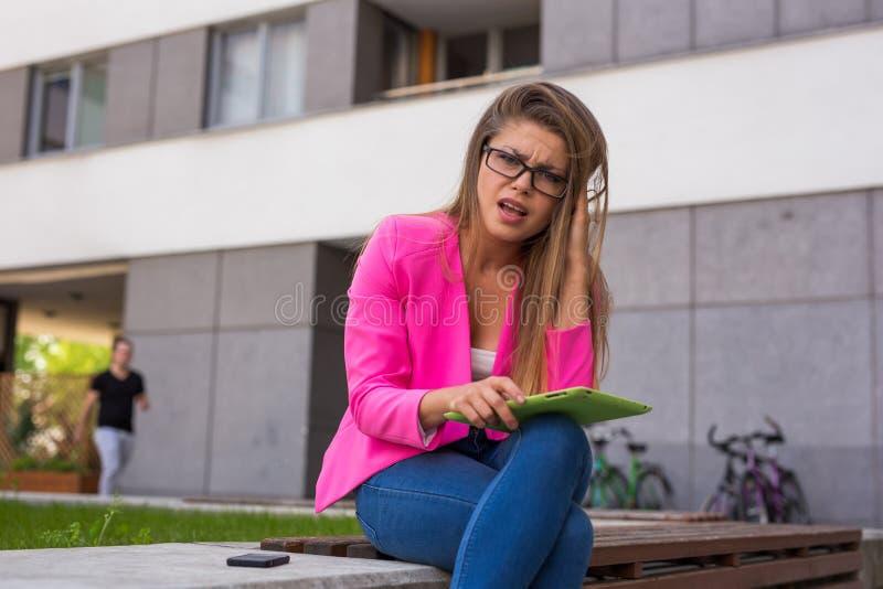 在片剂的美丽的年轻女实业家读书电子邮件 她有 免版税库存照片