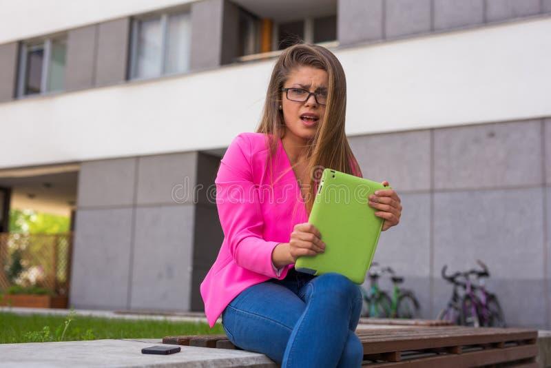 在片剂的美丽的年轻女实业家读书电子邮件 她有 免版税库存图片