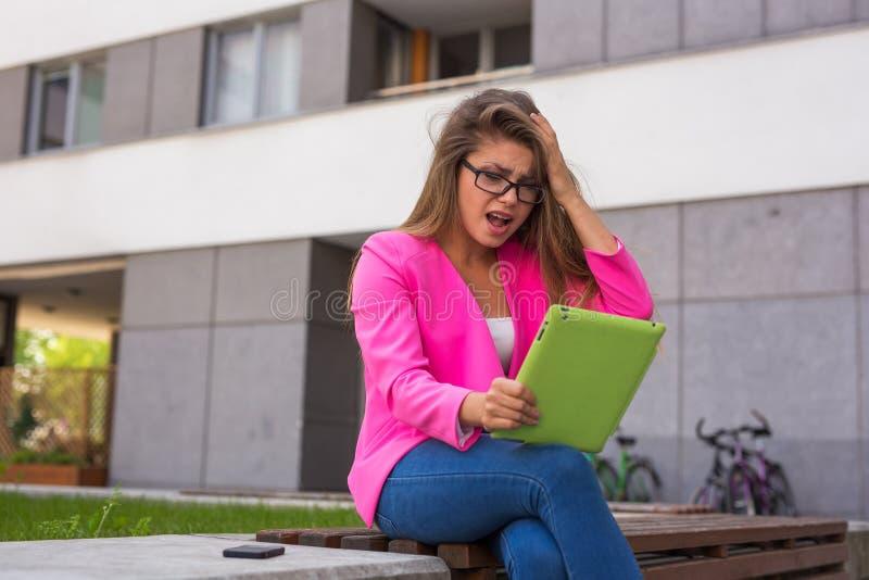 在片剂的美丽的年轻女实业家读书电子邮件 图库摄影
