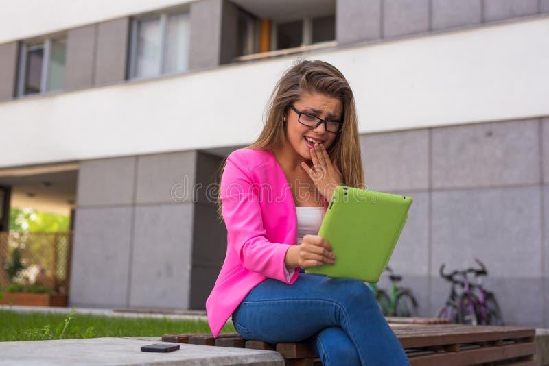 在片剂的美丽的年轻女实业家读书电子邮件 库存图片