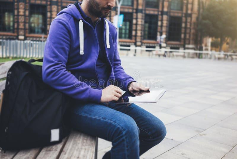 在片剂计算机或技术黑屏大模型的行家正文消息 有背包的微笑年轻人使用数字 免版税库存照片