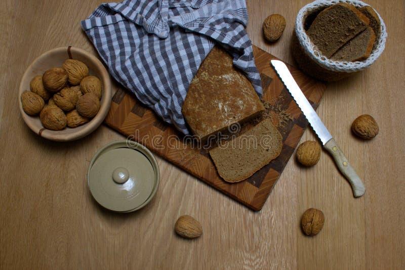 在片断和有些核桃切的惊人的家庭做的面包在边 免版税库存图片