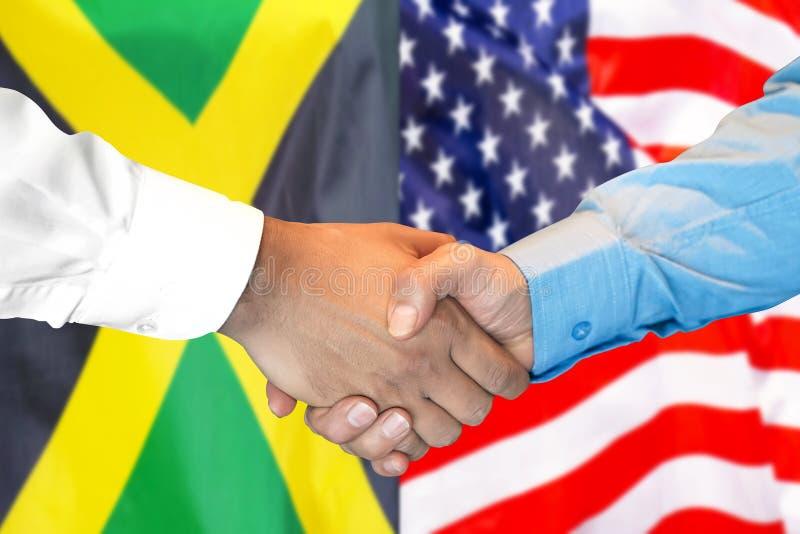 在牙买加和美国旗子背景的握手 免版税图库摄影