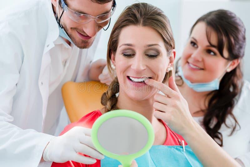 在牙齿漂白的以后的妇女在牙医 免版税库存照片