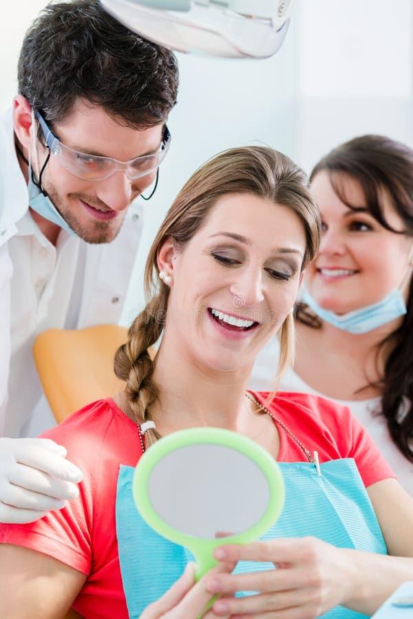 在牙齿漂白的以后的妇女在牙医 免版税库存图片