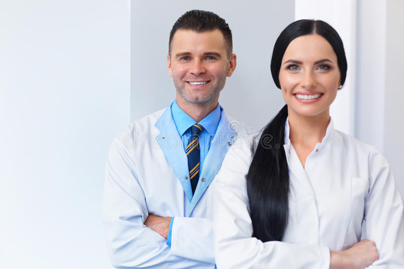 在牙齿诊所的牙医队 两位微笑的医生在他们的工作 免版税库存照片