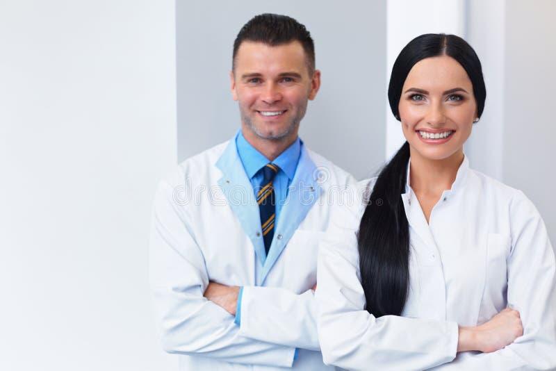 在牙齿诊所的牙医队 两位微笑的医生在他们的工作 库存图片