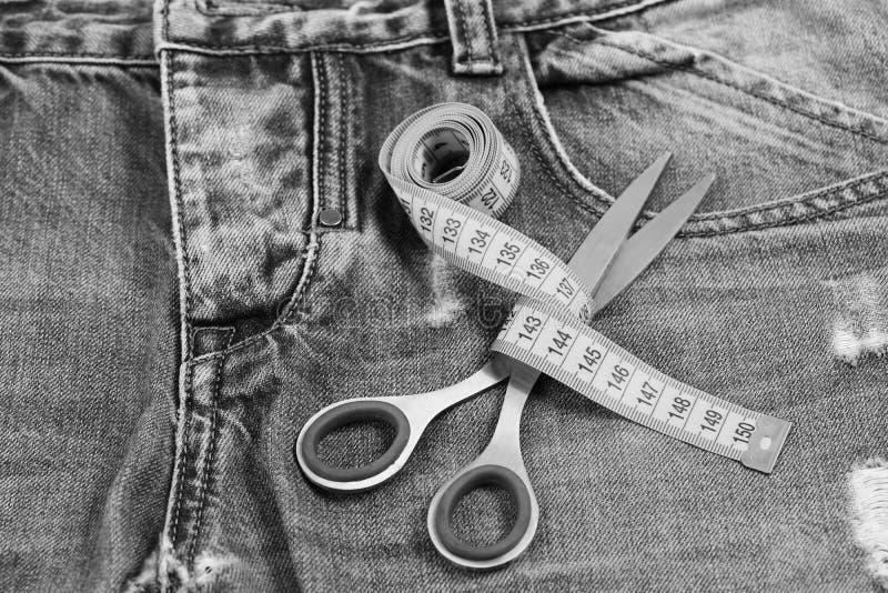 在牛仔布的裁缝工具:在金属剪刀附近受伤的措施磁带 免版税图库摄影