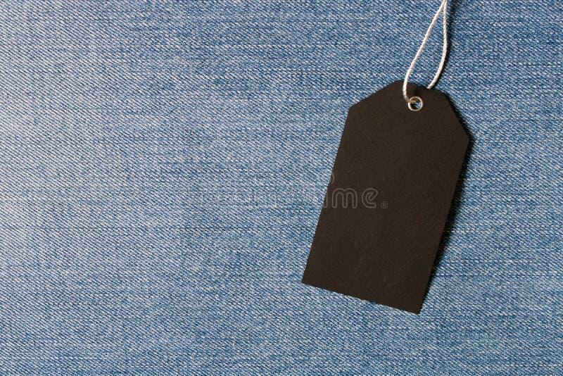 在牛仔布背景的空的黑标签 空的文本空间 免版税库存照片