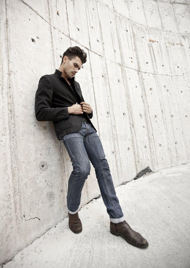 在牛仔裤和启动打扮的可爱的人 库存图片