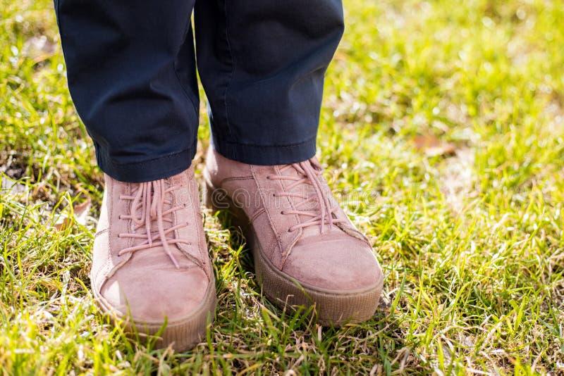在牛仔裤和桃红色运动鞋的女性腿在绿草,春日 免版税库存照片