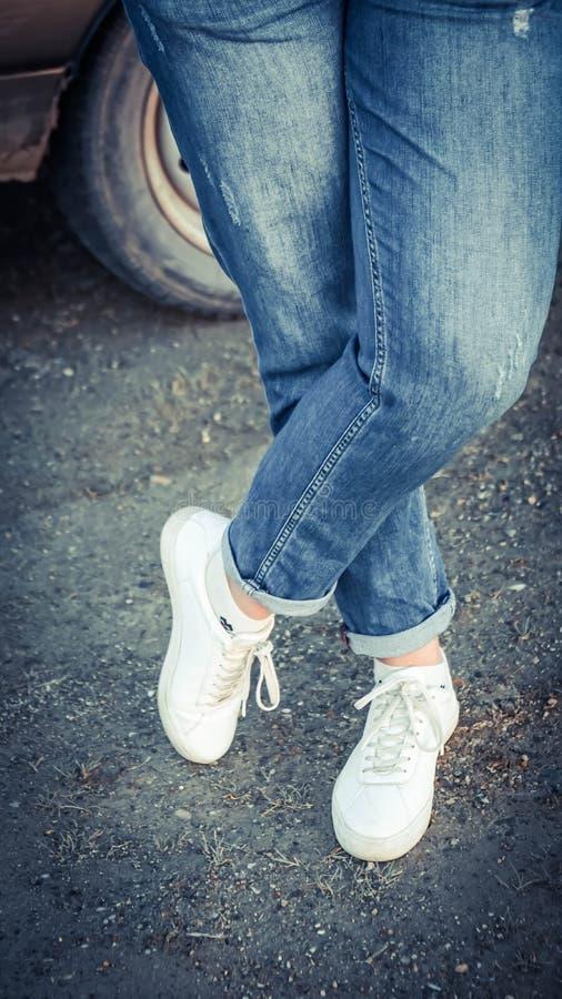 在牛仔裤和白色运动鞋的妇女的脚在地面时尚样式生活方式鞋子 免版税库存图片