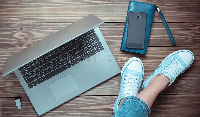 在牛仔裤和运动鞋,膝上型计算机,智能手机,在一个木地板上的一个钱包的女性腿 现代技术 一代Z 免版税库存图片