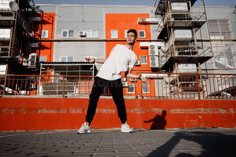 在牛仔裤和T恤杉打扮的年轻人跳舞在街道的现代舞在都市大厦背景在的 库存图片