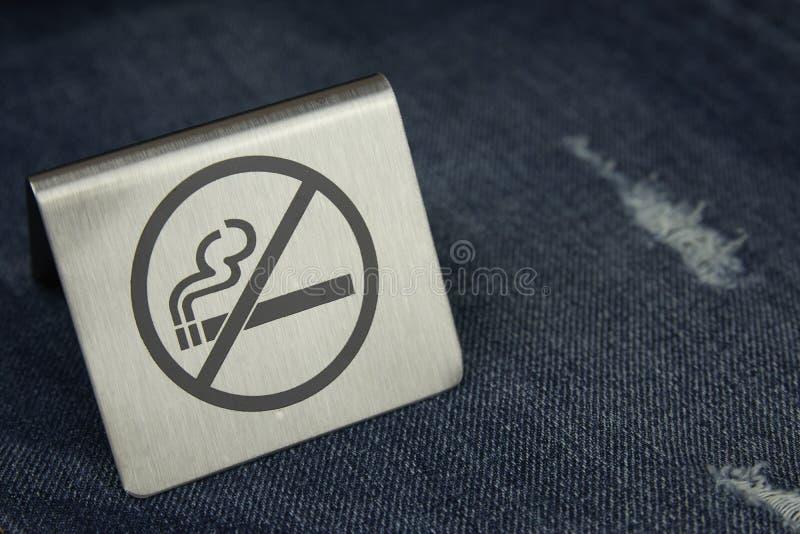 在牛仔裤的标志禁烟特写镜头 抽烟的杀害 库存照片