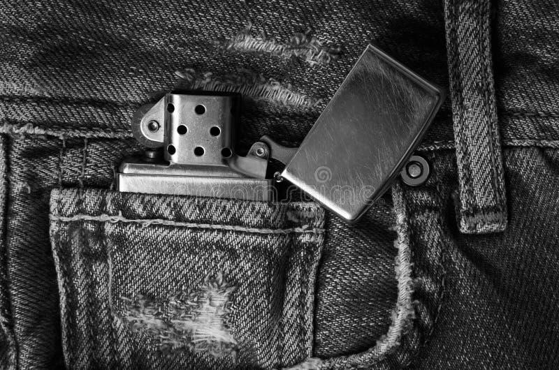 在牛仔裤的金属打火机 免版税库存图片