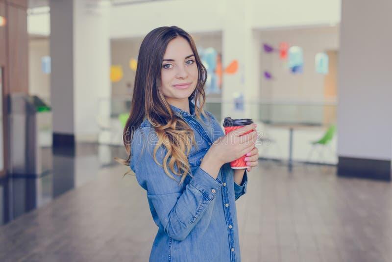 在牛仔裤衬衣打扮的迷人的微笑的愉快的妇女喝拿铁,当做在购物中心外带的咖啡店去的购物wa时 库存图片