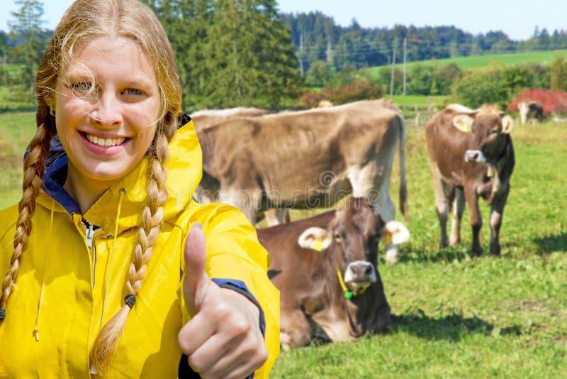 在牛前面的女孩 免版税库存图片