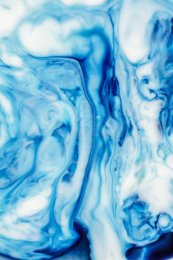 在牛奶摘要背景,大理石的食用染料喜欢 免版税库存图片