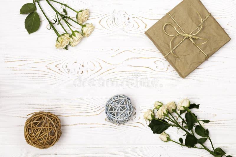 在牛皮纸、麻线、玫瑰米黄小花和在一个白色桌面的藤条球包裹的礼物盒 平的位置 复制空间 免版税库存照片