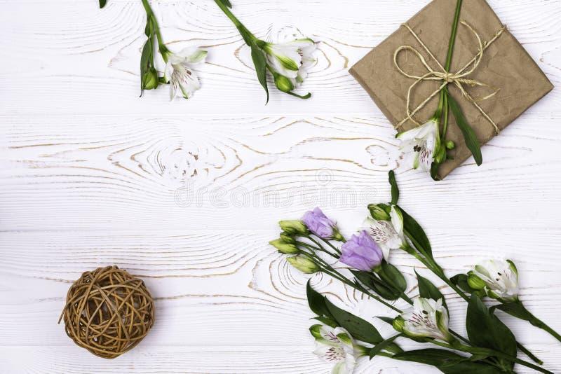在牛皮纸包裹的礼物盒和花和麻线在白色台式 平的位置 复制文本的空间 免版税库存照片