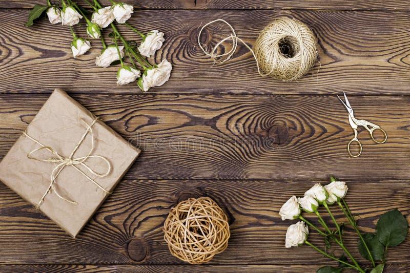 在牛皮纸或当前箱子从上面包裹的礼物和花、麻线和剪刀在木背景 平的位置 免版税库存照片