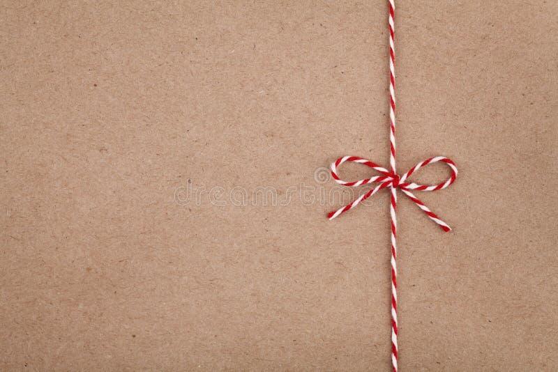 在牛皮纸纹理的弓或麻线栓的圣诞节串 免版税库存照片