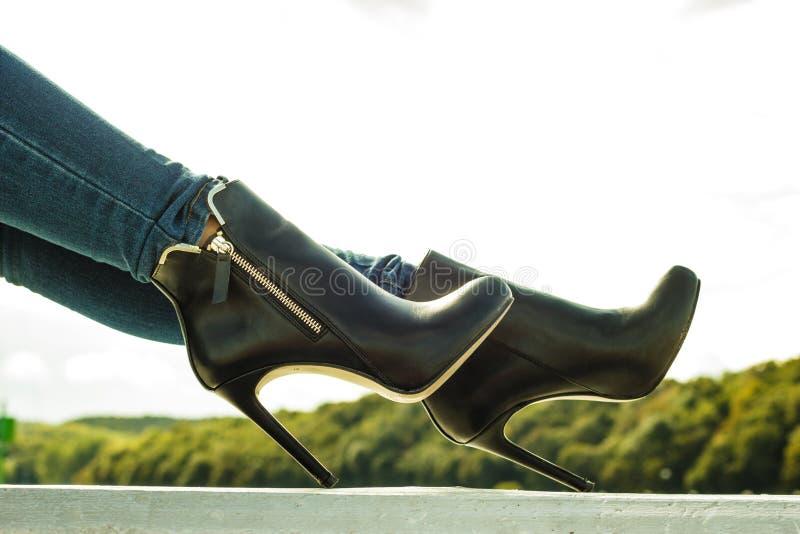 在牛仔布的妇女腿气喘室外脚跟的鞋子 库存图片