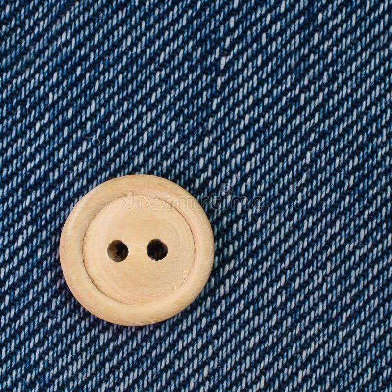 在牛仔布的木按钮 库存图片