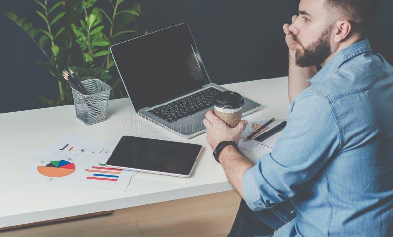 在牛仔布衬衣的年轻有胡子的商人在办公室在桌上,谈话坐手机和饮用的咖啡 库存图片