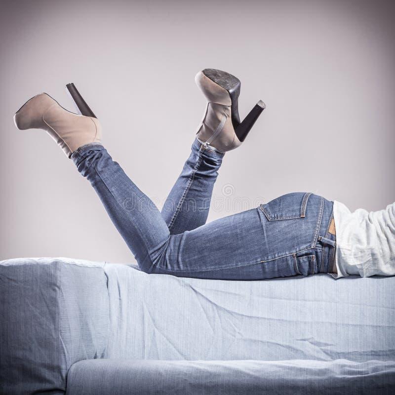 在牛仔布长裤高跟鞋鞋子的妇女腿 免版税库存照片