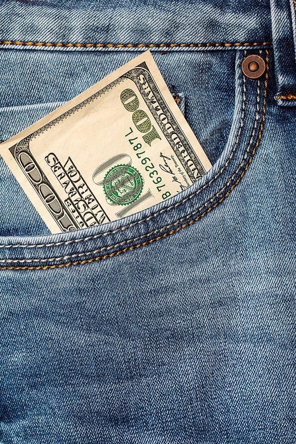 在牛仔裤口袋特写镜头的美元钞票 免版税图库摄影