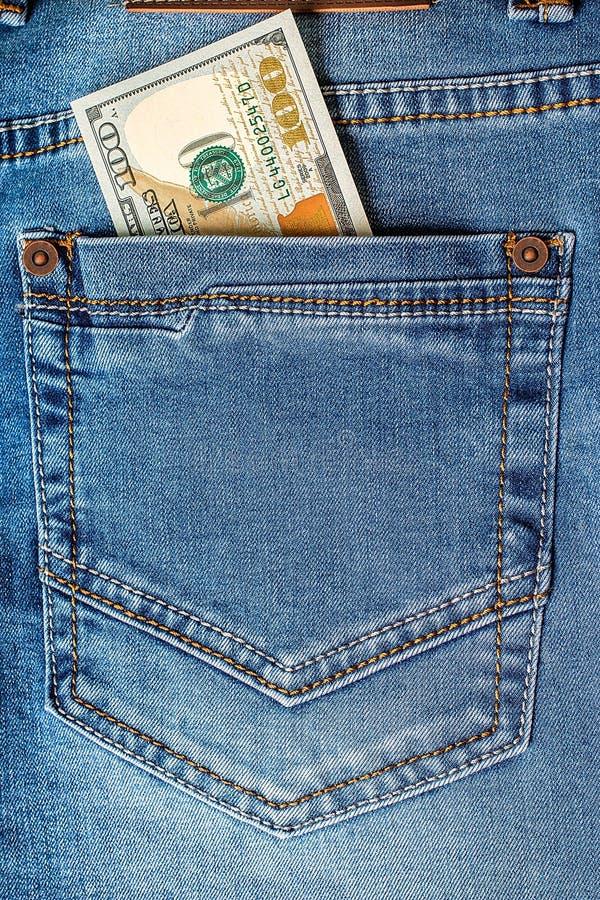 在牛仔裤口袋特写镜头的美元钞票 库存照片
