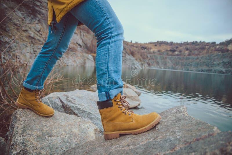 在牛仔裤和远足起动的女性腿临近山湖边缘  免版税库存照片