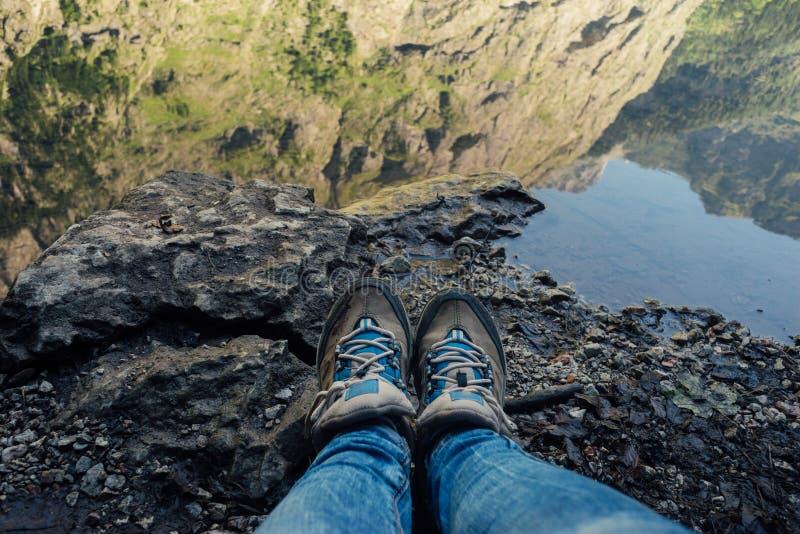 在牛仔裤的女性腿和远足起动反对山湖 免版税图库摄影
