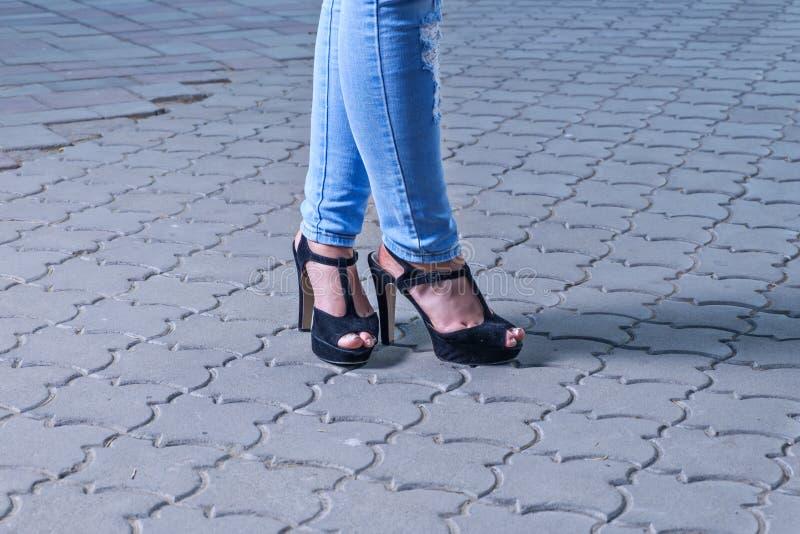 在牛仔裤的腿在高跟鞋 库存图片