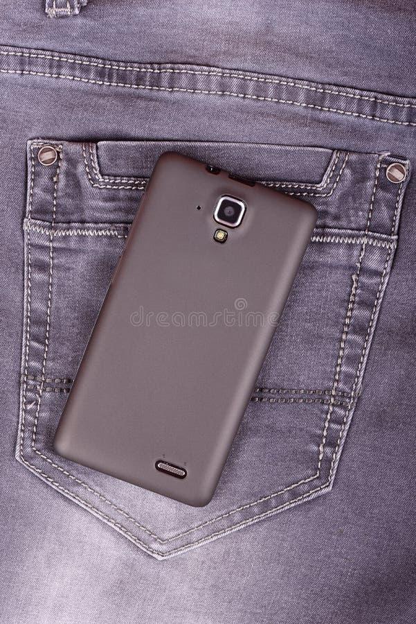 在牛仔裤背景的手机 库存图片