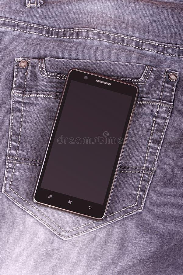 在牛仔裤背景的手机 免版税库存照片