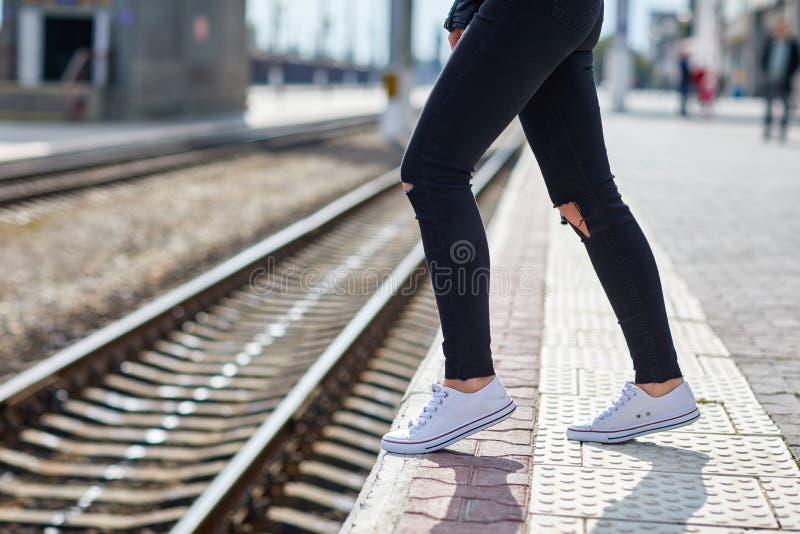 在特写镜头路轨的背景的女孩腿 免版税库存照片