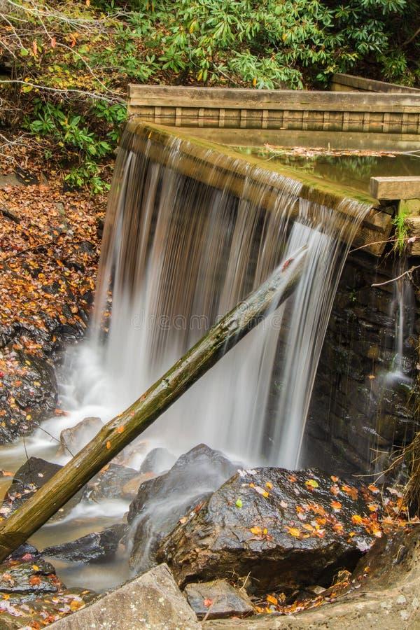 在犁耙磨房池塘水坝的秋天 库存图片