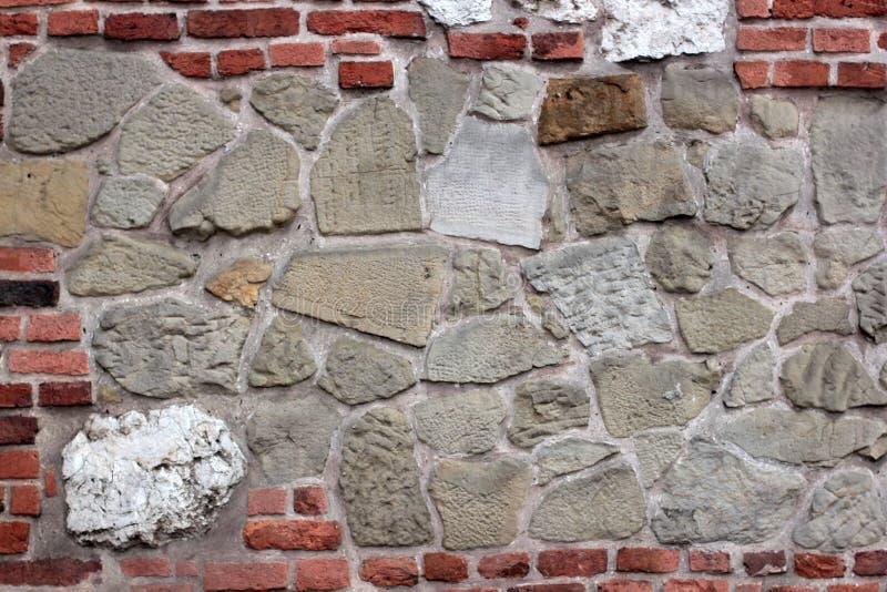 在犹太教堂附近的老腐朽的墙壁从砖和大石头克拉科夫,波兰 库存图片