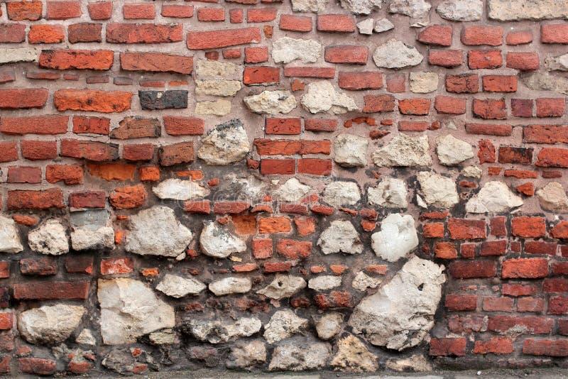 在犹太教堂附近的老腐朽的墙壁从砖和大石头克拉科夫,波兰 免版税库存照片