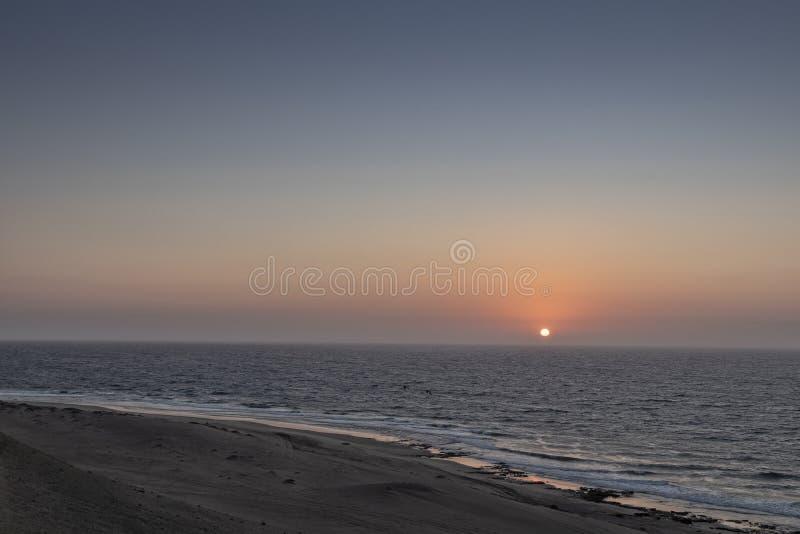 在狂放的纳米贝省海滩的美好的日落与峡谷和沙漠 库存照片
