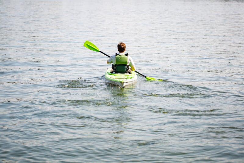 在独木舟的人划船 免版税库存图片