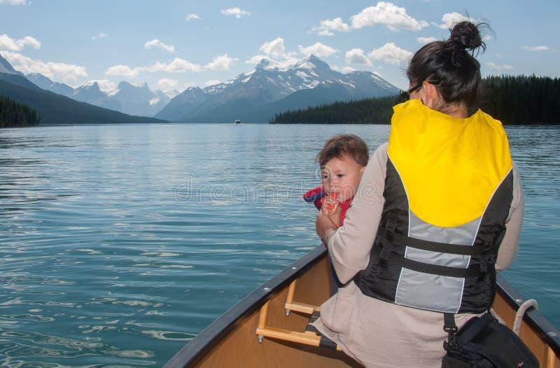 在独木舟的婴孩吹的口哨与母亲 免版税库存图片