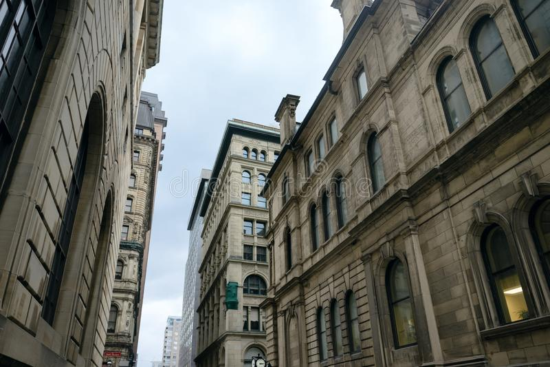 在狭窄的城市街道上的石办公楼 免版税图库摄影
