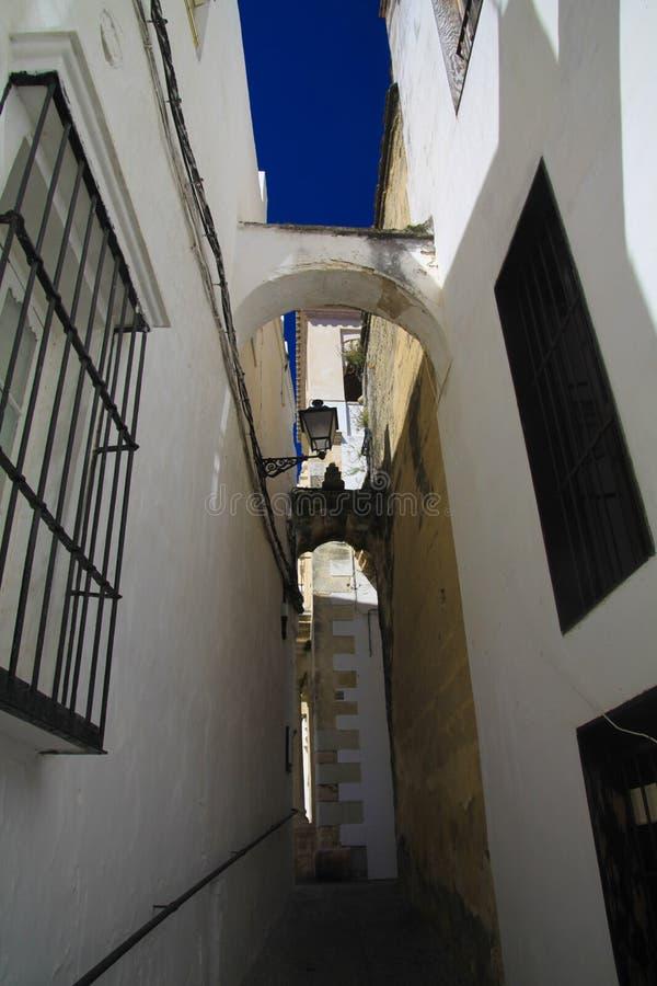 在狭窄的空的胡同的低角度视图有白色房子和步门面的在楼上与在传统的深蓝天空形成对比 免版税库存照片