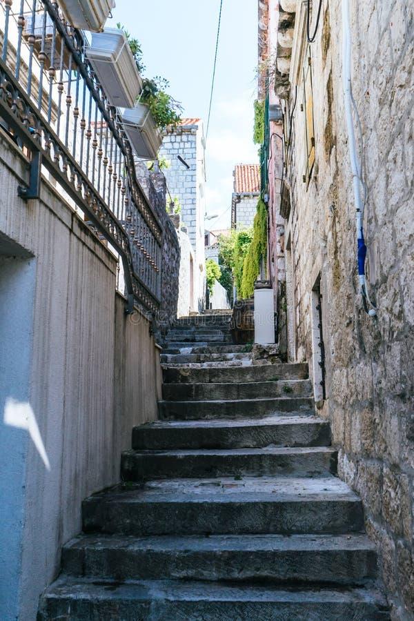 在狭窄的街道上的石台阶在中世纪墙壁中在克罗地亚的小镇 台阶在城市 老墙壁和金属篱芭与 图库摄影
